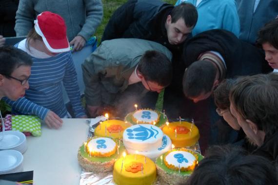 des personnes handicapées soufflent les bougies d'un gateau