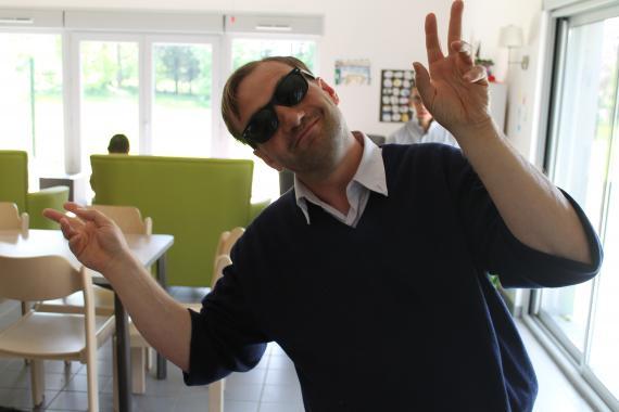 personne handicapée avec lunette de soleil faisant un signe joyeux