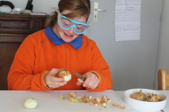 personne trisomique pele un oignon dans la cuisine