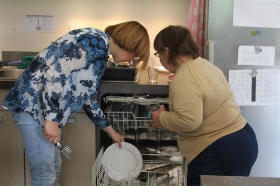 une personne handicapée range la vaisselle avec une assistante