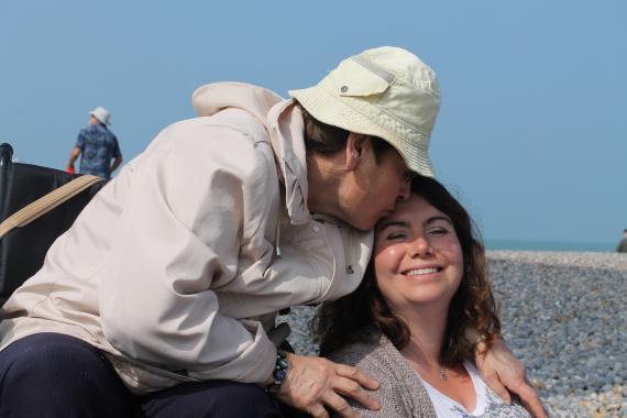 une personne handicapée embrasse tendrement une jeune fille sur le front