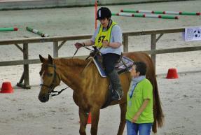 personne ayant un handicap mental monte à cheval à côté d'un accompagnant