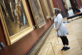 une femme regarde un tableau au louvre