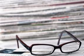 paire de lunette à côté d'une pile de journal